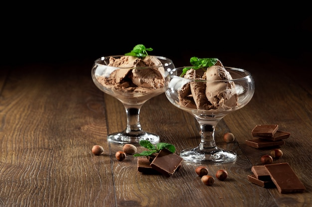 Homemade chocolate ice cream with mint leaves, sprinkled with chocolate in a glass bowl on a wooden table