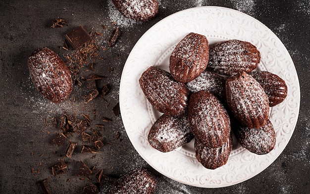 Homemade chocolate madeleines on dark table