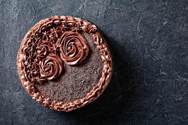自家製チョコレートメレンゲケーキにチョコレートバタークリームのバラをトッピング、上からの水平方向のビュー、フラットレイ、コピースペース
