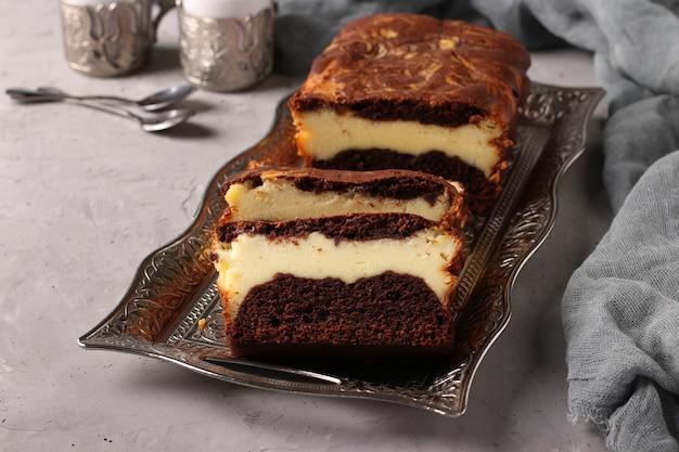 灰色の背景、クローズアップ、水平形式の金属トレイにあるカッテージチーズと自家製チョコレートマフィン