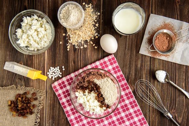 暗い木製のテーブルの白いプレート上のカッテージチーズと自家製チョコレートオートパンケーキ。