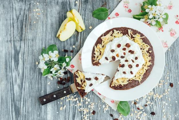 アップル、ヨーグルト、カッテージチーズ、レーズン、灰色の木製の背景の花と自家製チョコレートオートパンケーキ。