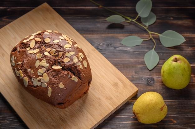 나무 보드에 생강과 카 다몬으로 만든 초콜릿 배 케이크