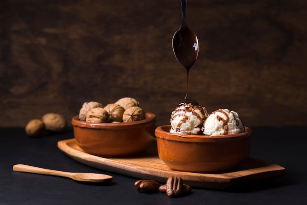 Homemade chocolate pouring on ice cream scoops