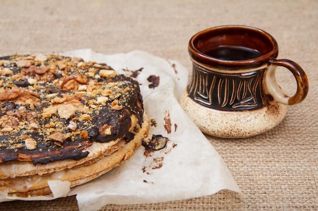 荒布の上に自家製チョコレートパフケーキと茶色の粘土のコーヒーカップ。