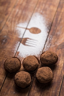 Homemade chocolate truffle candies with cocoa powder near the spoon and fork shape on sugar powder