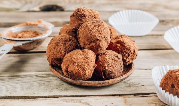 Rustcの木製の背景にココアを振りかけた皿の上の自家製チョコレートトリュフキャンディボール。トップビュー