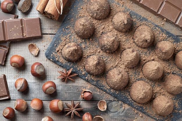 素朴な古いキッチンテーブルに、ココアパウダーをまぶした自家製チョコレートトリュフとナッツやその他のスパイスを添えたチョコレートの盛り合わせ。上面図。