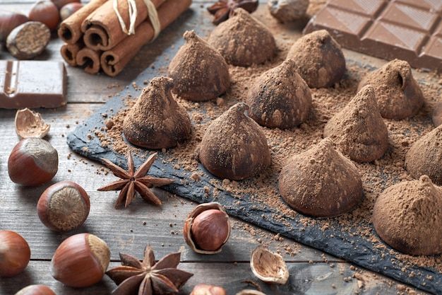 Домашние шоколадные трюфели, посыпанные какао-порошком, и шоколадное ассорти с орехами и другими специями на деревенском старом кухонном столе.