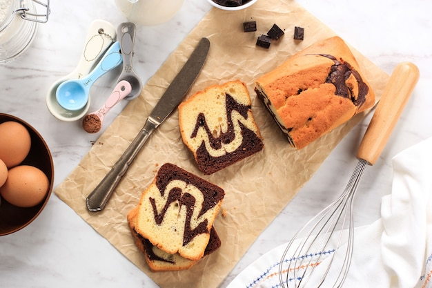 Homemade chocolate and vanilla marble loaf cake. sliced served with tea or coffe. served on oval ceramic plate white background