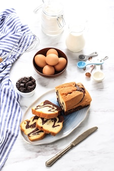 Homemade chocolate and vanilla marble loaf cake. sliced served with tea or coffe. white background