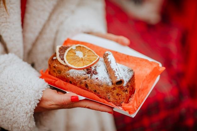 В руках женщины домашний рождественский торт с цукатами, сушеными апельсинами, орехами и корицей. руки с красным маникюром и белым зимним пальто. концепция праздничной еды.