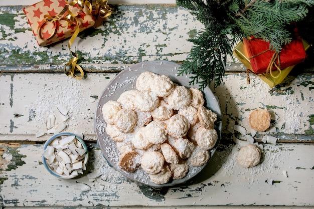 クリスマスの贈り物や装飾が施された古い木製のテーブルのセラミックプレートにココナッツフレークが付いた自家製のクリスマスココナッツグルテンフリークッキー。フラットレイ