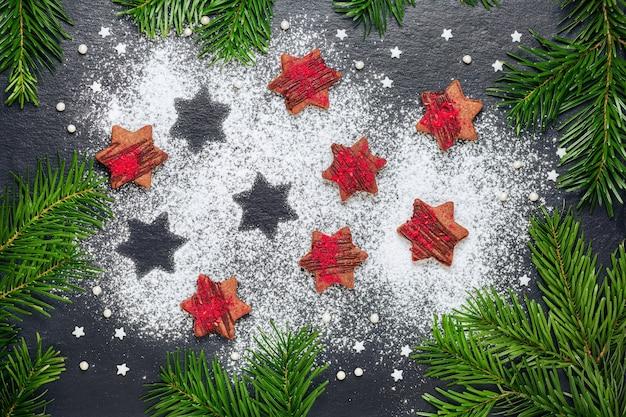 소나무 가지와 슬레이트 테이블에 설탕 가루와 나무 딸기 철 커 덕으로 만든 크리스마스 쿠키 초콜릿 별