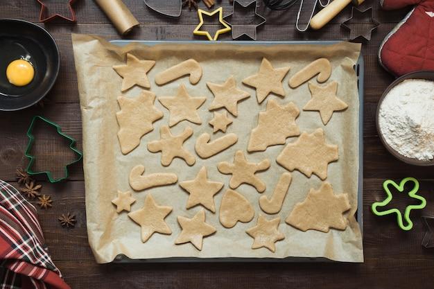Домашнее печенье рождество на пергаменте. xmas. процесс выпечки домашнего печенья. вид сверху.