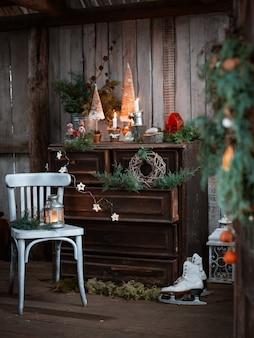 Самодельные новогодние украшения на деревенской террасе со старинным комодом и подсвечниками ручной работы в честь рождества.
