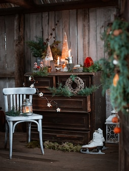 Homemade christmas decorations on a rustic terrace with a vintage chest of drawers and handmade candlesticks to celebrate christmas