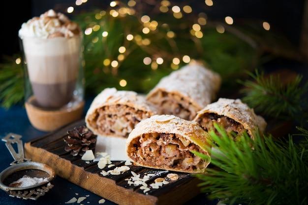 집에서 만든 크리스마스 디저트, 사과 슈트루델, 화환이 있는 축제 테이블에 있는 케이크, 선별적인 집중