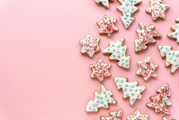 Домашние рождественские пряники в виде звездочек и елок на розовом