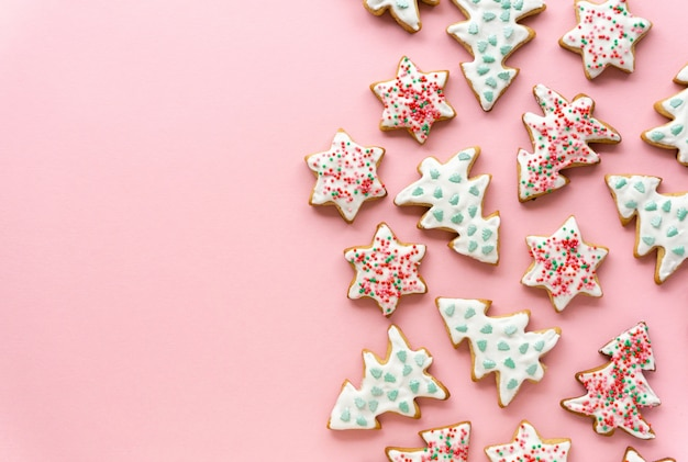 Homemade christmas gingerbread cookies in the shape of stars and trees on a pink