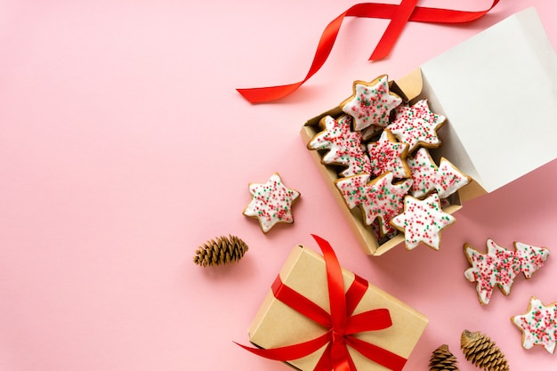 Homemade christmas gingerbread cookies in the shape of trees and stars in gift box on pink