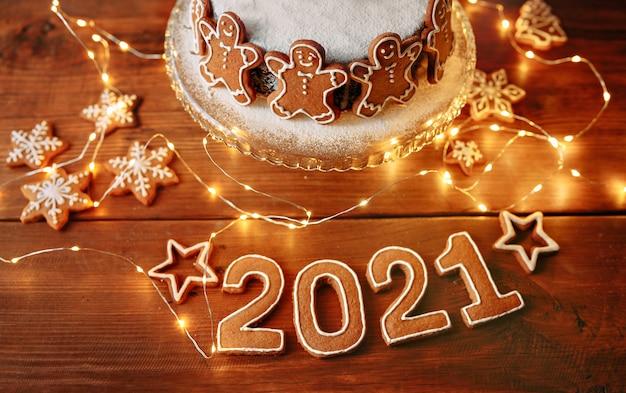 Домашний рождественский пирог, украшенный печеньем, фигурки людей, на коричневом вуденском столе с числами нового года и огнями