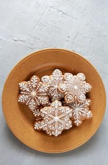 自家製のクリスマススノーフレークの形のジンジャーブレッドを皿に。平面図、クローズアップ、ライトグレーのコンクリートの背景。