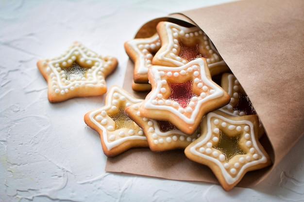 白い背景の上の紙のパッケージで自家製のクリスマスの星の形の砂糖キャラメルクッキー