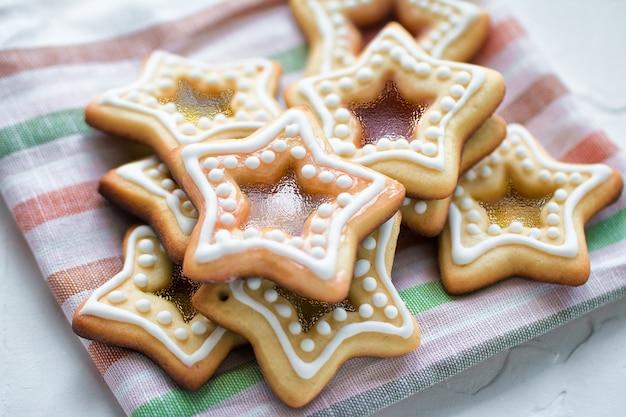 白い背景の上の色の縞模様のナプキンに自家製のクリスマスの星の形の砂糖キャラメルクッキー