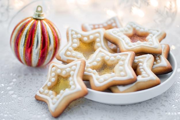 白い背景の上の自家製クリスマス星形砂糖キャラメルクッキー
