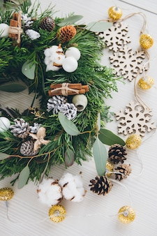 Homemade christmas wreath on white wooden table