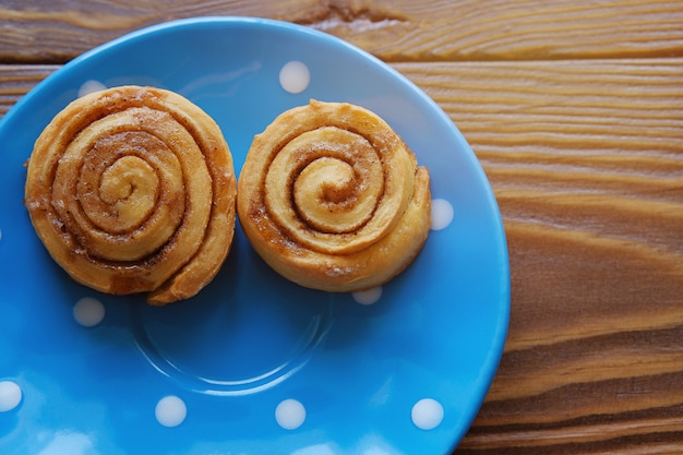 Homemade cinnamon rolls on a blue plate stand on a wooden table