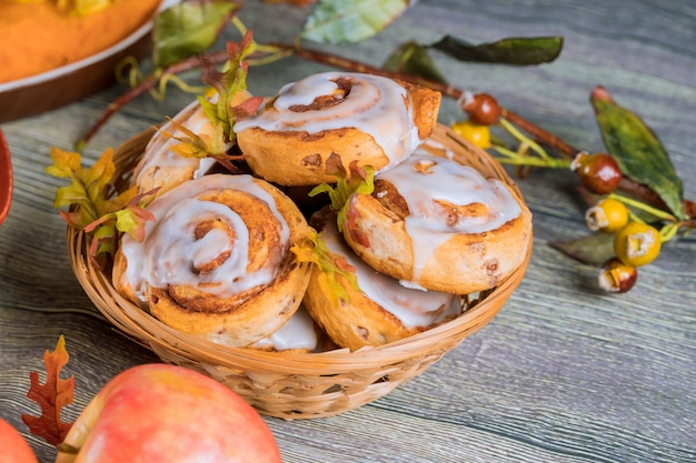 Homemade cinnamon rolls with white glaze and apple.