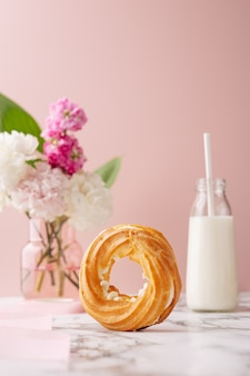Домашний круговой профитроль с заварным кремом, покрытый сахарной пудрой на мраморном столе
