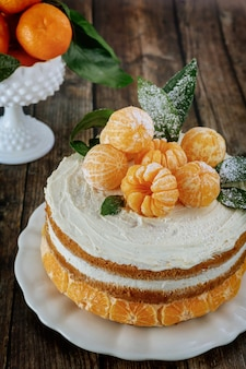 Homemade citrus cake decorated with fresh tangerines
