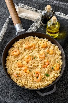 Homemade classic risotto with prawns in cooking pan
