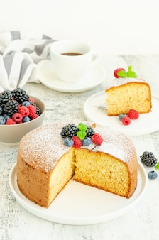 Homemade classic vanilla sponge cake or biscuit sprinkled with powdered sugar and fresh berries on top on a white plate on a light wooden background.