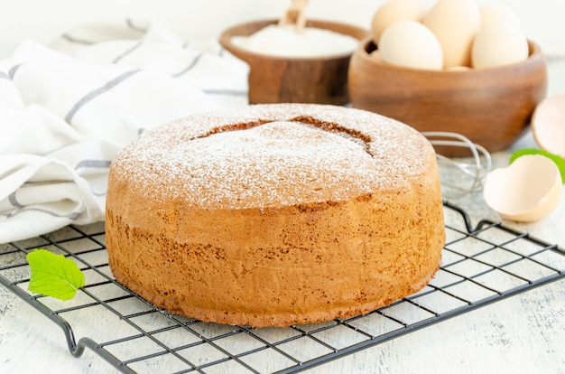Homemade classic vanilla sponge cake or biscuit sprinkled with powdered sugar on a grill on a light wooden background.