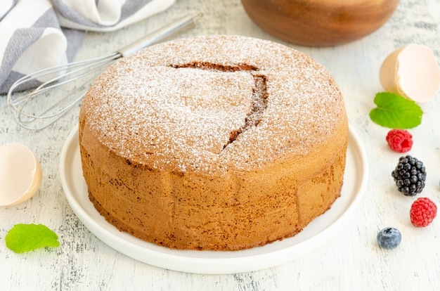Домашний классический ванильный бисквит или бисквит, посыпанный сахарной пудрой и свежими ягодами на белой тарелке на светлом деревянном фоне.