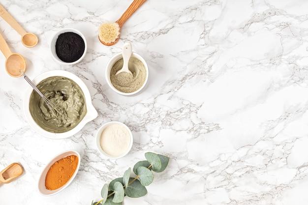 Самодельная маска для лица из глины. безотходные экологически чистые ингредиенты для косметических товаров на светлой стене, плоская планировка, вид сверху