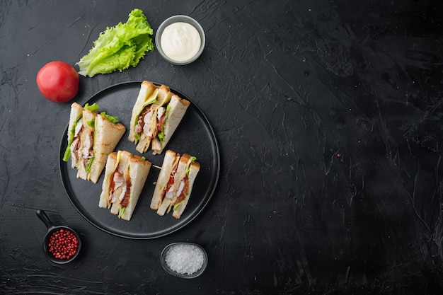 Homemade club sandwich made with turkey, bacon, ham, tomatoes, on black background, top view with copy space for text