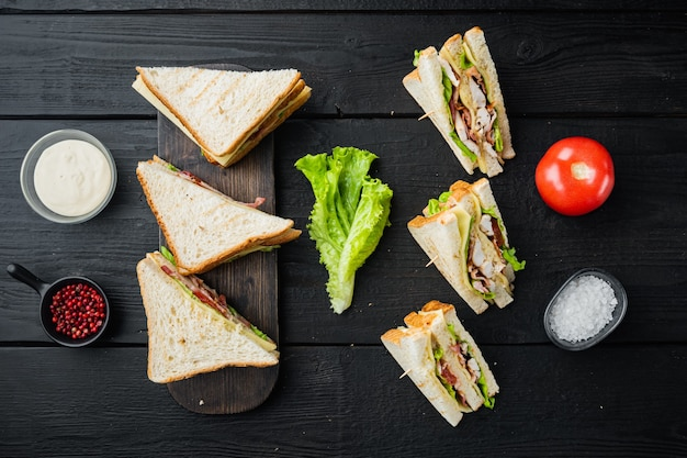 Homemade club sandwich made with turkey, bacon, ham, tomatoes, on black wooden background, top view