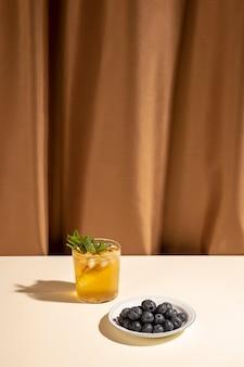 茶色のカーテンの近くの白いテーブルの上の皿にブルーベリーと自家製カクテルドリンクグラス