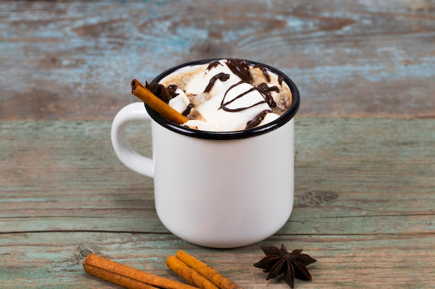 Homemade cocoa mug with marshmallows cinnamon and star anise on wooden