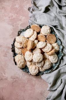 ピンクのテクスチャー表面のセラミックプレートにココナッツフレークが入った自家製ココナッツグルテンフリークッキー。フラットレイ、コピースペース