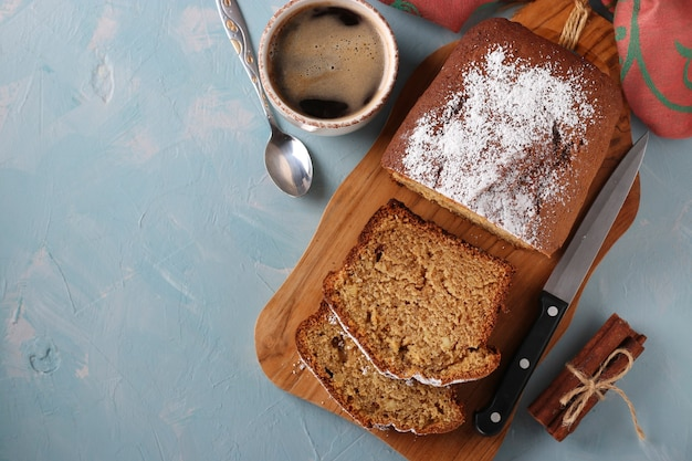 Homemade coffee muffin on a wooden board and a cup of coffee on a light blue background, copy space, top view