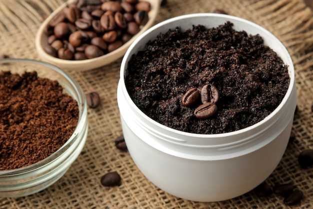 Homemade coffee scrub in a white jar for the face and body and various ingredients for making scrub.