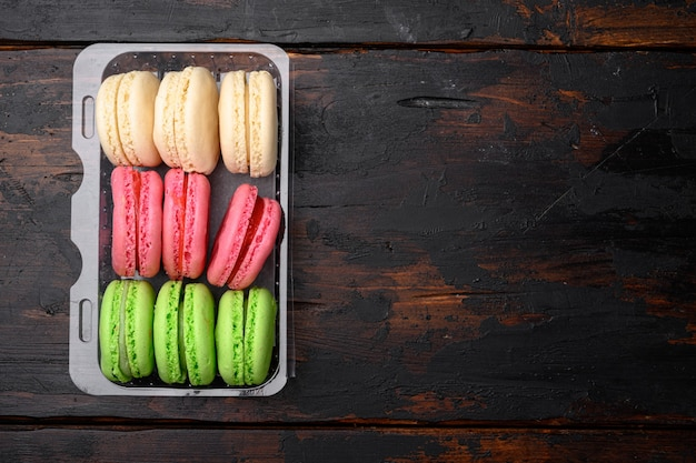 Homemade colorful macaroons set, in plastic pack, on old dark  wooden table background, top view flat lay, with copy space for text