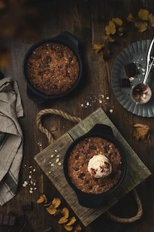 Домашняя комфортная еда, гигантское печенье на сковороде с шоколадной крошкой и мороженым, вид сверху