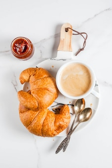 Homemade continental breakfast, coffee croissants. jam on white marble table, copyspace top view